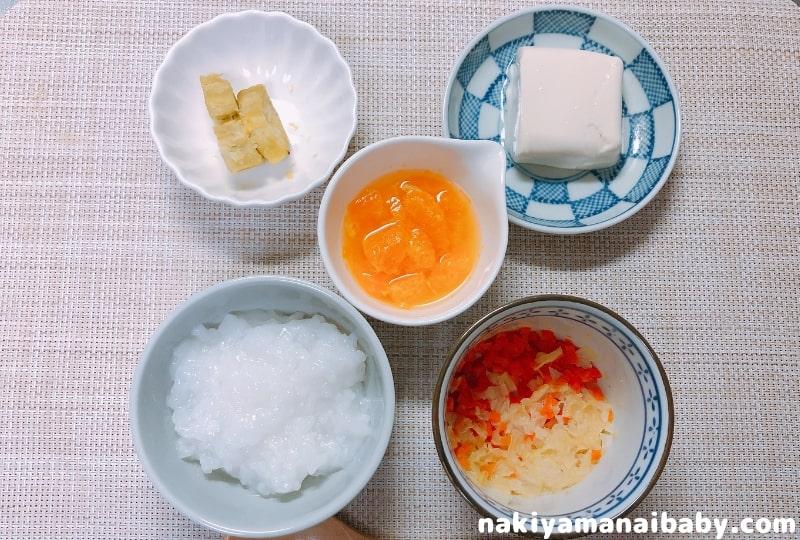 野菜のだし煮の献立例。おかゆ、野菜のだし煮、豆腐、さつまいも、みかんかぼちゃの写真
